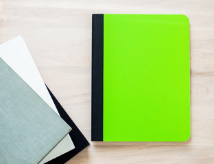 back to school-bright green notebook with blank cover for customized title, next to worn text books on a wooden desk