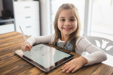 Little Girl Drawing Picture on Digital Tablet Using Stylus