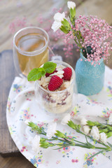 Green tea and muesli with berries and yogurt for breakfast. Healthy food. Vegetarian and vitamins. A bouquet of flowers in a vase. Text. Vertical photo