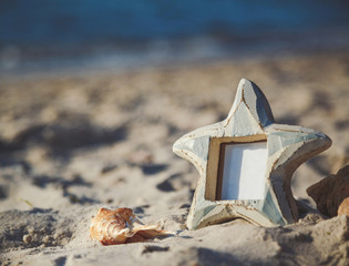 Blank empty photo frame with copy space at the sandy beach