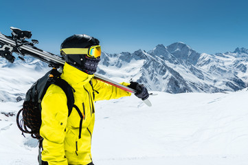 A large portrait of a skier in a protective helmet and glasses is a mask and scarf with skis on his shoulder in the snow-capped mountains of the Caucasus. Skiing,