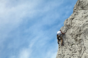 Man climbs to the top of the mountain. Rock climbing with belaying. Learning to climb a mountain. To reach a top.