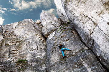 The woman climbs to the top of the mountain. A young girl on a climbing wall under the open sky. Climbing the rope and climb the mountain.The woman climbs to the top of the mountain. A young girl on a