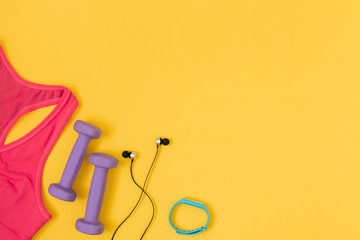 Sports and fitness accessories on yellow background. Flat lay, top view.