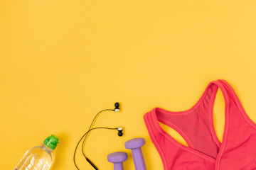 Sports and fitness accessories with water on yellow background. Flat lay, top view.