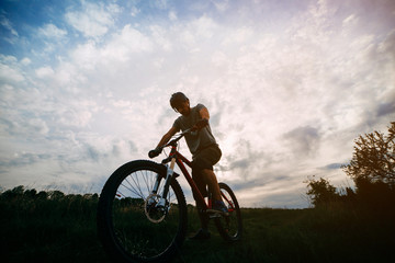 Bicycle sports, traveling, healthy lifestyle and activity. Silhouette of young man riding bicycle along a country road in sunset light