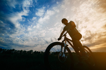 Sports, tourism and activity concept. Silhouette of a cyclist in helmet riding a bicycle over sunset sky background