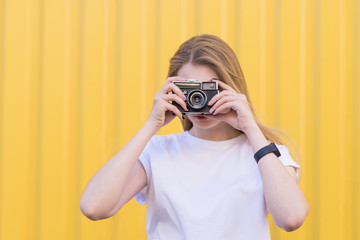 Blond girl is standing on a yellow background and making a photo on an old film camera. Girl with a retro camera on a colored background.