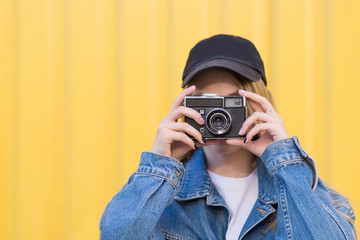Close-up portrait of a smiling young girl with a film camera in her hands on a yellow background. The girl in a jeans jacket is photographed on a film.