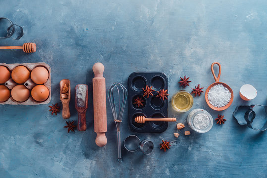 Making pastry flat lay with wooden scoops, whisks, cookie cutters, muffin tin, sugar, flour, eggs and cinnamon on a modern concrete background with copy space. Baking tools and ingredients from above.