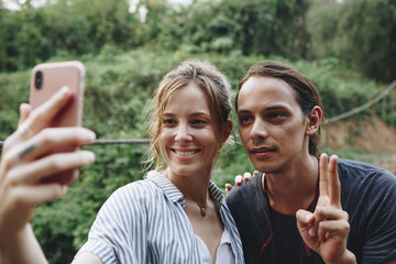 Caucasian woman and man taking a selfie outdoors recreational leisure, freedom and adventure concept