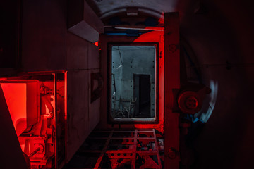 Gateway corridor of airlock of abandoned bunker. Big hermetic door illuminated by red lantern