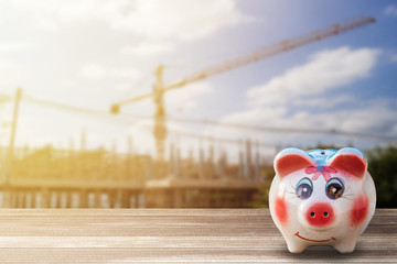 Piggy Bank on wood desk and blur construction background.