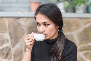 Asian woman holding white cup and drinking a hot coffee or tea in cafe.