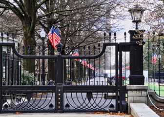 Security fence outside of drive leading into White House grounds in Washington DC, as flags flap in the wind on a rainy day.