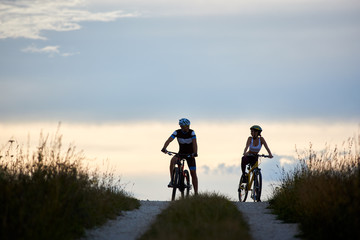 Couple of cyclists sitting on bicycles on a country road watching each other in the background a horizon with a beautiful evening sky. The guys are dressed in sports clothes and helmets