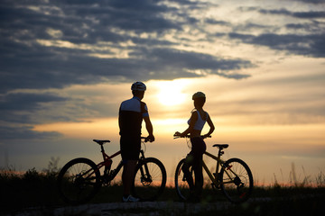 Back view of a couple of cyclists standing with bicycles and enjoying the sunset. A guy and a girl are dressed in helmets and sportswear. Perfect sky with clouds and evening sun