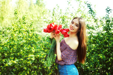 Young woman in spring Park . Girl holding red tulips in a blooming garden