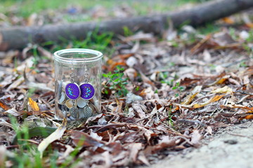 Silver with purple fabric elements handmade earrings hang on glass jar on the ground among autumn leaves in the forest