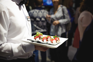Waiter carrying trays with food. Caterring service for wedding, birthday or any company event