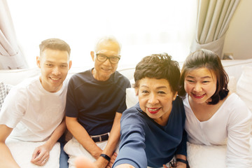 Asian family with adult children and senior parents taking selfie and sitting on a sofa at home. Happy and relaxing family time