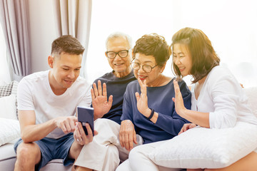 Asian family with adult children and senior parents making a video call and waving at the caller at home