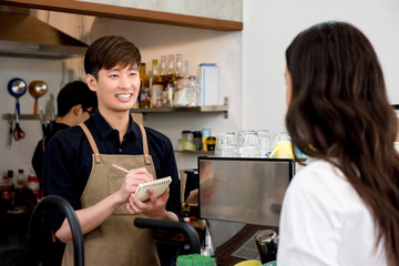 Asian man staff taking order from the customer in coffee shop