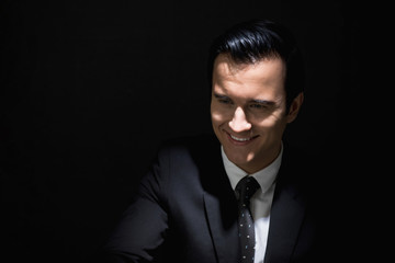 Cunning businessman smiling in shadow