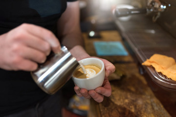 baristas pours milk in coffee cup