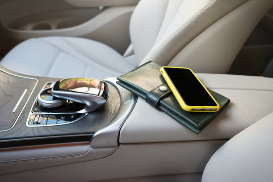 A telephone and purse lie on an elbow-rest in the salon of car