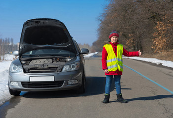 Boy in a waistcoat on the road near a car with a prolate hand, asks a technical help.