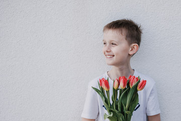 Young boy holding a bunch of red tulips and smiling aside. Giving a bouquet as a gift. White wall background, copy space.