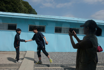 A woman takes a picture of boys mimicking a handshake between North Korean leader Kim Jong Un and South Korean President Moon Jae-in at the summit in late April, at the replica of the truce village of Panmunjom at a movie studio in Namyangju