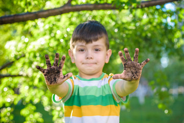 A young Caucasian boy showing off his dirty hands after playing in dirt and sand