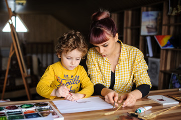 Young mother looking at her son and explaining how to draw