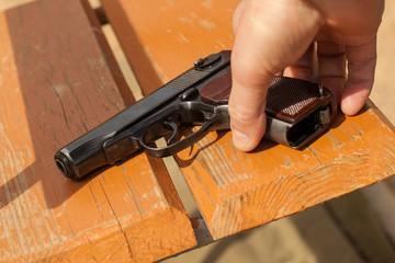 A man's hand takes a gun