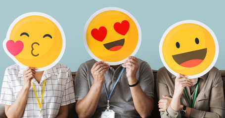 Cheerful people holding emoticon icon