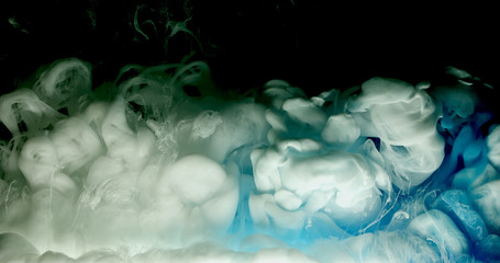 Blue and white acrylic paint cloud spraying in water on black background.