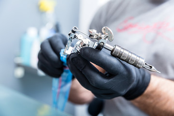 Close-up of the hands of a skilled tattoo artist wearing black gloves while setting a sterile machine for tattooing in a modern studio