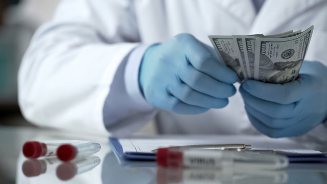 Doctor hands counting money on table, financing clinic experiments, bribery