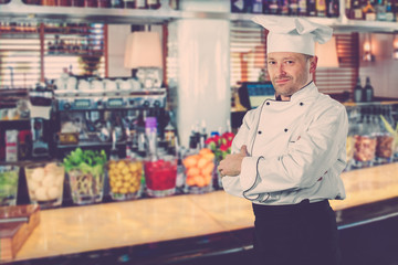 The chef is a white man in uniform, Bar counter. In bright retro colors.