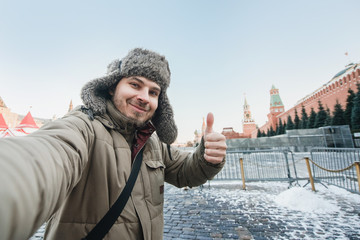 tourist man takes a photo of himself against the background of a red square in winter in Moscow, Russia. Shows a thumbs-up, gesture of good humor.