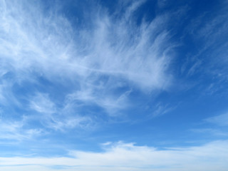 White feathered clouds in the blue sky. Beautiful sky background with cirrus clouds