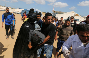 Wounded demonstrator is evacuated during a protest where Palestinians demand the right to return to their homeland, at the Israel-Gaza border in the southern Gaza Strip