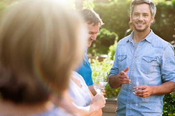 Portrait of a man in a group of friends gathered  in a garden on a summer evening to share a meal and have a good time together