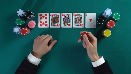 Lucky man has royal flush hand, wins much money in poker game, enjoying success