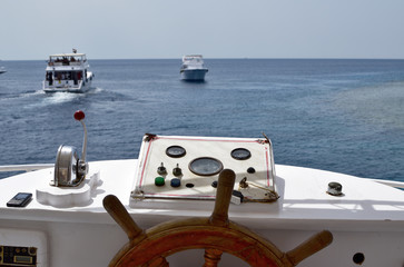 Ship with wooden steering wheel and navigation console at the helm of a yacht or motor boat, follows other yachts on the high seas. nobody in the frame.