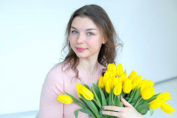 Portrait of a young woman in a bright room. Woman with a bouquet of flowers of yellow tulips.
