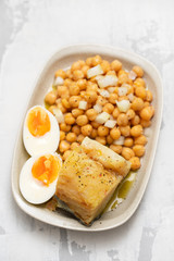 cod fish with chick pea and boiled egg on dish