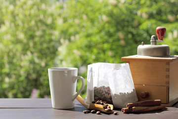 natural hot coffee/ white mug with cinnamon sticks and coffee beans is on the table on a background of a blooming spring garden